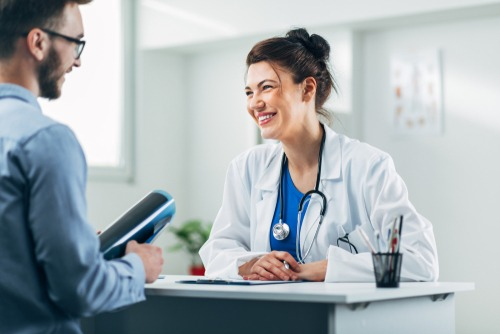 Smiling female doctor wearing lab coat and stethoscope consults with happy male patient at a small table in her office.