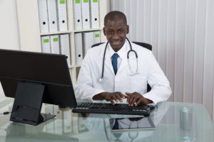 Smiling male doctor wearing lab coat and stethoscope sits at glass table in office, typing on desktop computer's keyboard.